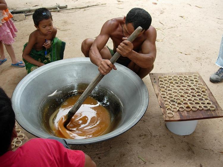 Un paysan remuant le sucre de palme
